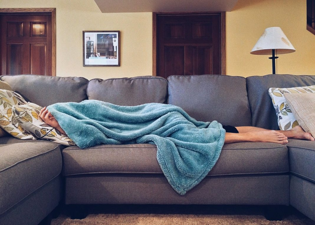 Person sover under et tæppe på sofaen