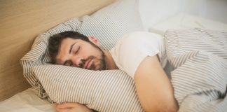 Mand sover i sin seng