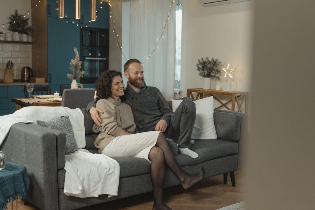 Kærestepar sidder i sofa sammen