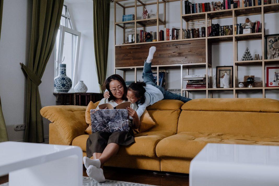 Kvinde sidder i sofa med et barn