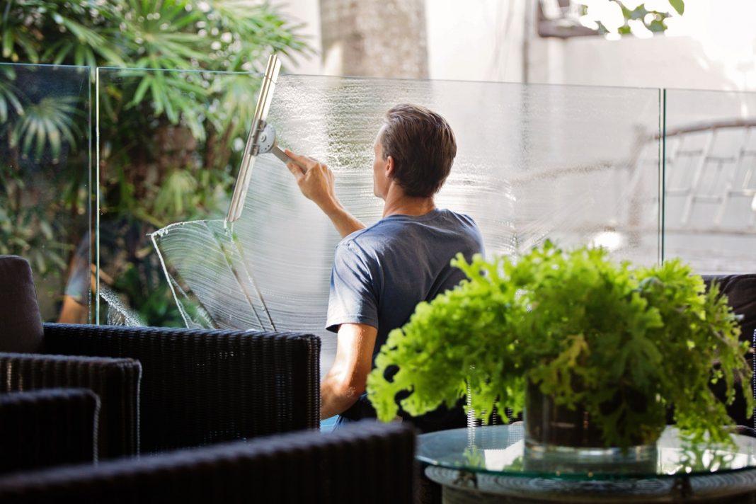 Mand pudser vinduer i gård